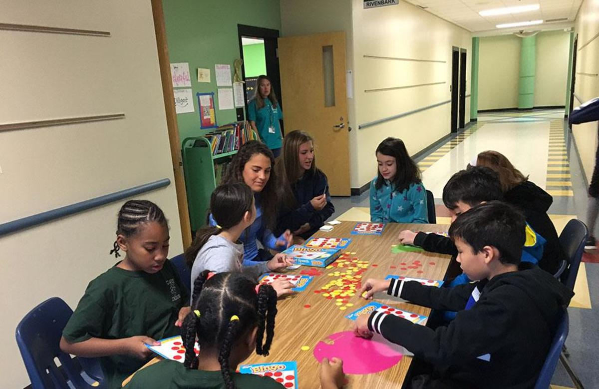 Soccer players Charlotte Teeter and Julia Schukle teach fourth graders the importance of math through a game of Bingo.