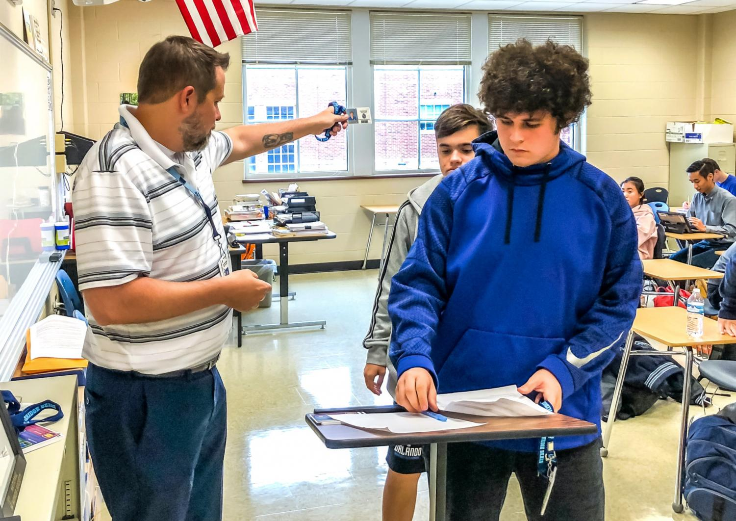 English teacher Jon Karschnik distributes new student IDs with lanyards to his students during one of his classes.