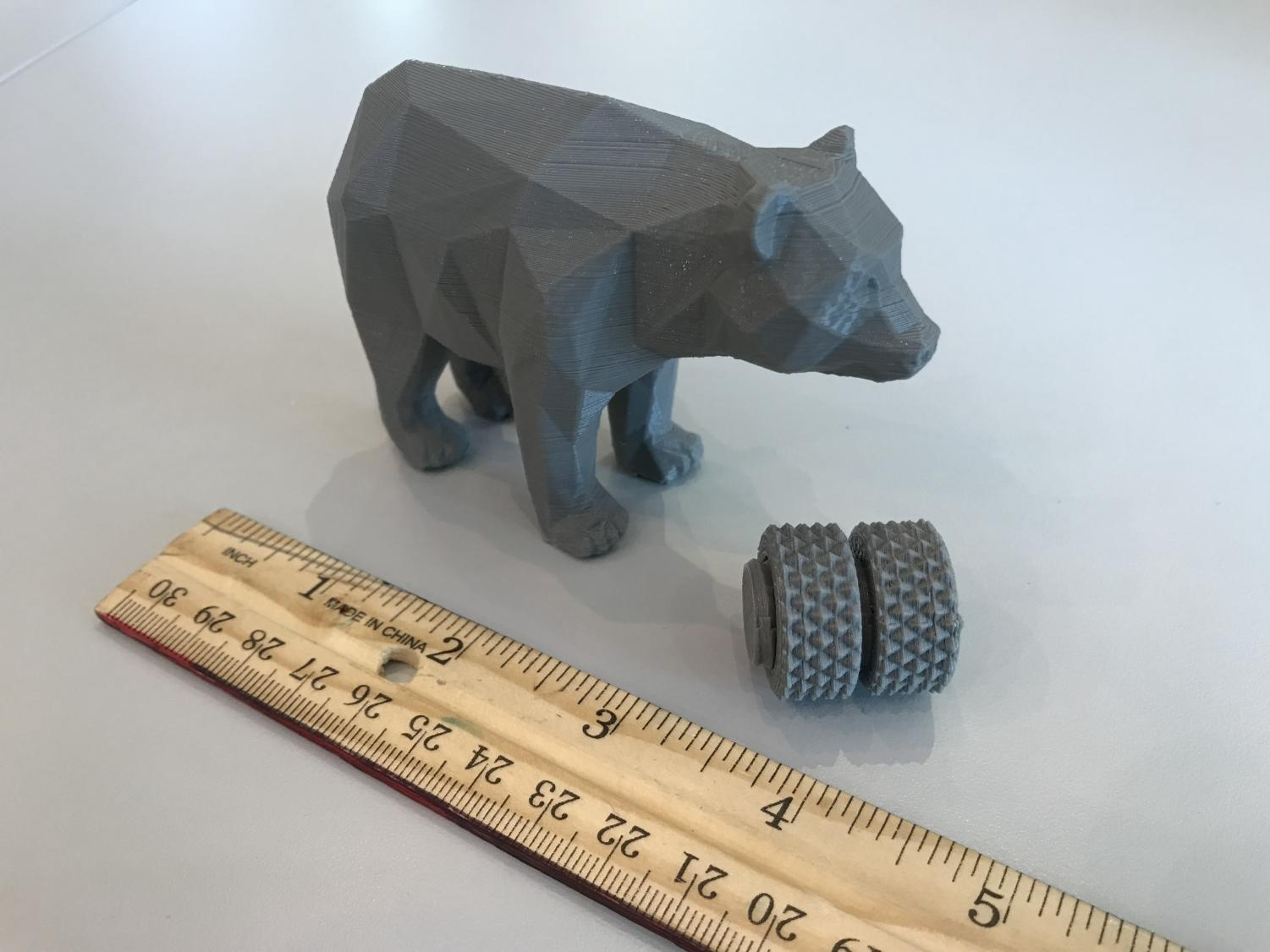 A plastic bear (roughly 2 x 3 x 2 in) made by the 3D printer.