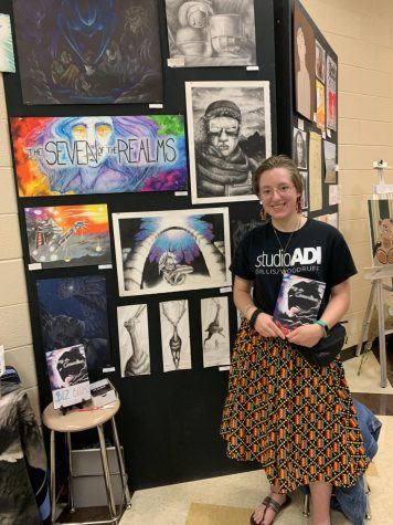 Sophomore Emily Phillips in front of her artwork.