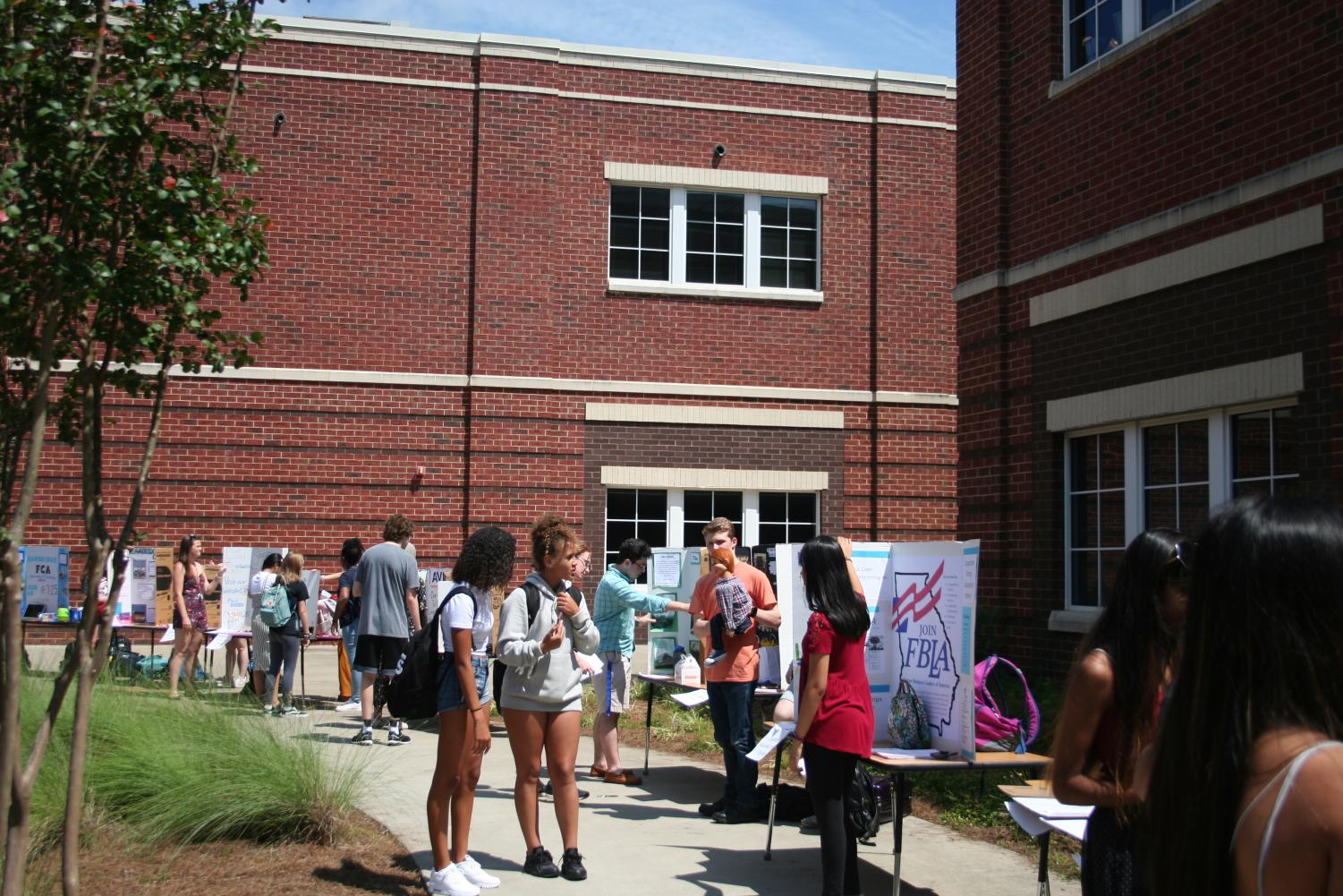 Students+browse+tables+at+the+club+fair.