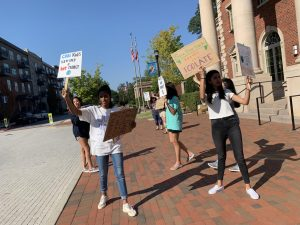 Students display homemade signs as they protest towards oncoming traffic.