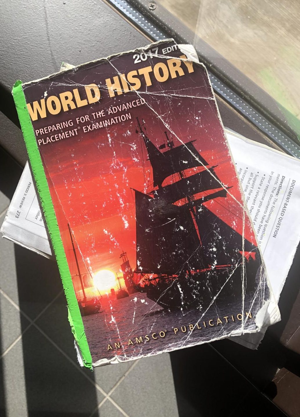 An illustrated photo of a 2017 edition AP World History book, nicknamed the AMSCO, ripped in half.
