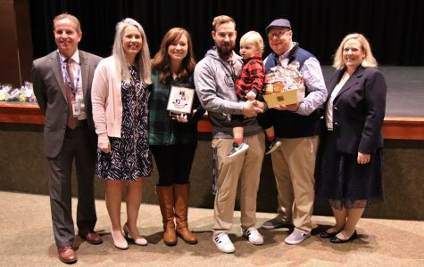 Teacher of the Year, Hal Funderburk, and his family holding his award and his baby.