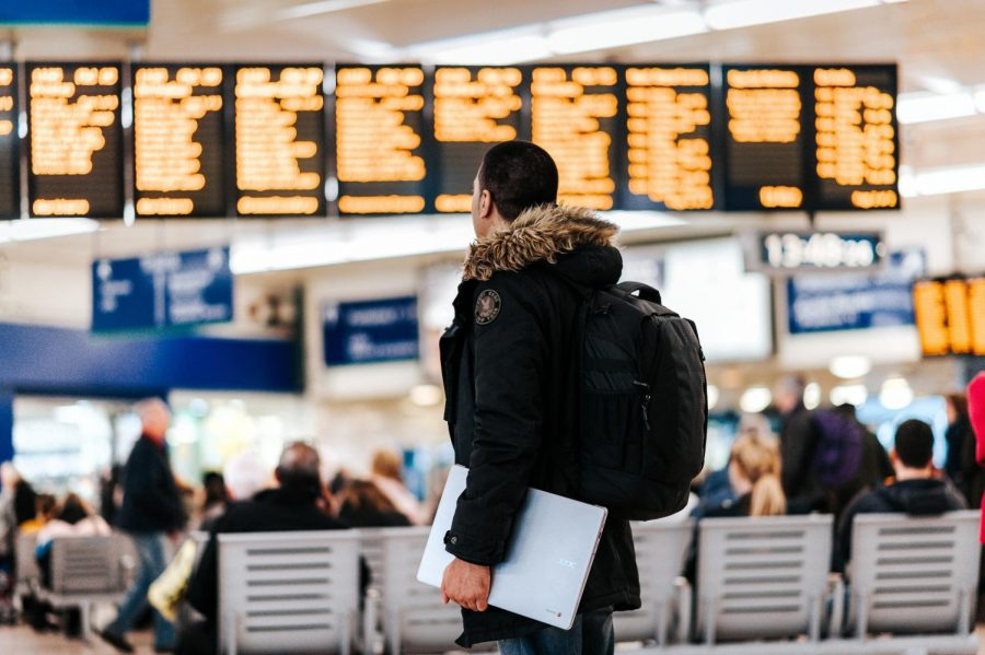 A man stands inside of an airport looking at the LED flight schedule.