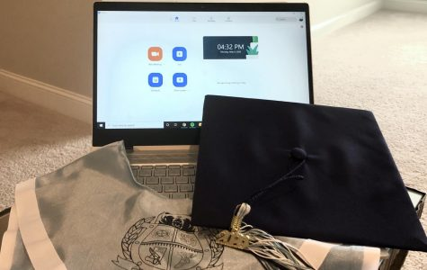 A graduation cap and Cambridge stole in front of a computer displaying the home screen for Zoom, a popular app for group video calls.