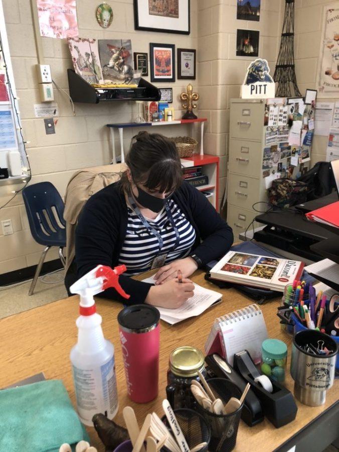 French teacher Colleen Baldridge grades quizzes at her desk.