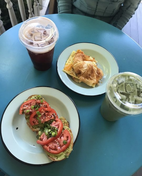 Harp's avocado toast topped with tomatoes and a drink of matcha.